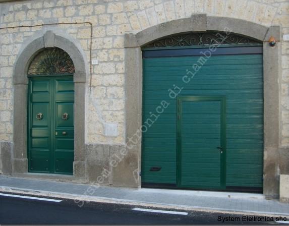 Porta sezionale verde con porta pedonale caprarola